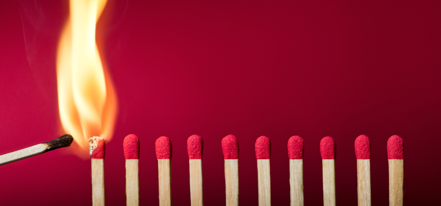 A lit match lighting a row of other matches